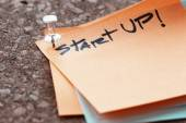 Close up on pin and strat up word on sticky note with cork board — Stock Photo