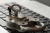 Internet security concept-miniature businessman stand on old key — 图库照片