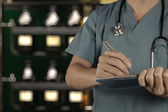 Smart doctor working with blurred vintage bottle with bokeh back — Stock Photo