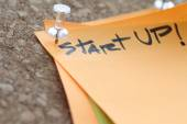 Close up on pin and start up word on sticky note with cork board — Stock Photo