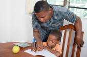 Dad helps his child to write at home. — Stock Photo