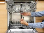 Handyman repairing a dishwasher — Stock Photo