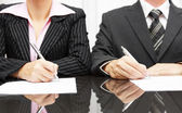 Businesswoman and businessman signing contract after negotiation — Stock Photo