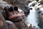 Limited focus old hiking boots in front of waterfall — Stockfoto