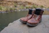 Old hiking boots beside river — Stockfoto