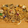Large Pile Of Gold Jewelry On Wood Counter — Stock Photo #71945011
