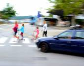 Dangerous city traffic situation with children and car — Stock Photo