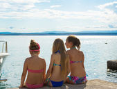 Three girls having rest on a beach — Stockfoto