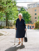 Old woman walking with a cane — Stock Photo