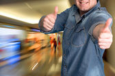 Young man gesturing thumbs up at shopping mall — Stock Photo