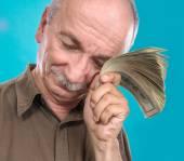 Lucky elderly man holding dollar bills — Stock Photo