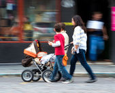 Mother with toddler child in stroller and children — Stock Photo