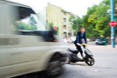 Dangerous city traffic situation with a motorcyclist and a bus — Stock Photo