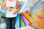 Woman holding shopping bags and credit card  — ストック写真