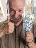 Lucky elderly man with dollar bills — Stock Photo