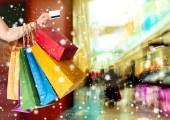 Woman holding credit card and shopping bags — Stock Photo