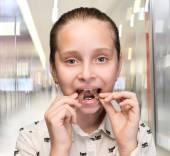 Happy girl holding braces — Stock Photo