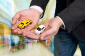 Businessman in black suit holding two small car models — Stock Photo