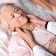Female doctor examining old woman — Stock Photo #60565571