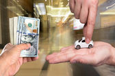 One man holding dollar banknotes, another man holding small car  — Stock Photo