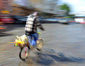 Woman on bicycle in motion riding down the stree — ストック写真