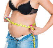 Overweight woman measuring waistline with centimeter — Stock Photo
