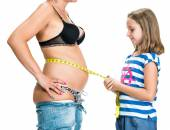 Daughter measuring mother's waistline  with centimeter — Stock Photo