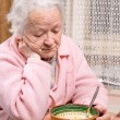 Old woman eating at home — Stock Photo #62153887