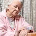 Old sad woman holding pills — Stock Photo #62153991