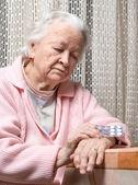 Old sad woman holding pills — Stock Photo