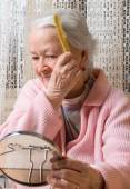 Old smiling woman combing her hair — Stock Photo