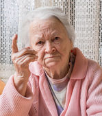 Portrait of  old woman in angry gesture — Stock Photo