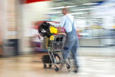 Worker in overalls pushing trolley in hardware shop — Stockfoto