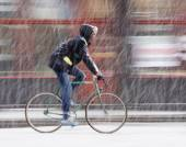 Man on bicycle in the city in snowy winter day — Stock Photo