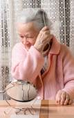 Old smiling woman combing her hair at home — Stock Photo
