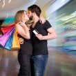 Happy kissing couple with shopping bags — Stock Photo #64502395