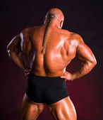 Bodybuilder  demonstrating muscles of the back and arms — Stock Photo