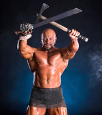 Handsome muscular ancient warrior with axe and sword — Stock Photo