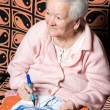 Old woman painting for fun — Stock Photo #68064875