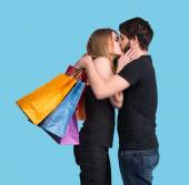Happy kissing couple with shopping bags — Stock Photo