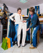 Shop assistant showing white jeans to beautiful gir — Stock Photo