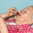 Old sick woman eating strawberry — Stock Photo #69887651