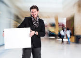Smiling handsome man with big blank board — Stock Photo