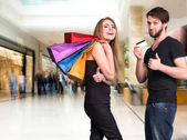 Happy couple with shopping bags at the mall — Stock Photo