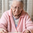 Old sad woman eating at home — Stock Photo #71897581