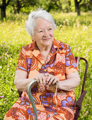 Beautiful smiling old woman sitting in the chair — Stock Photo