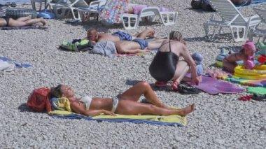 Primosten sunbathing on the beach — Vídeo de stock