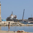 Rethymno port with cargo ships and lighthouse and sunbathers. Cr — Stock Photo #52445865