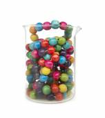 Little colorful wooden balls in a glass recipient — Stock Photo