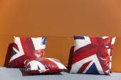Chill out zone with british colors cushions and orange wall — Stock Photo